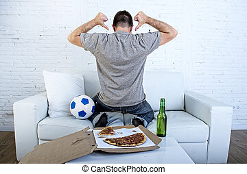 man celebrating goal at home couch watching football game on television