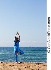 nurse doing yoga on beach