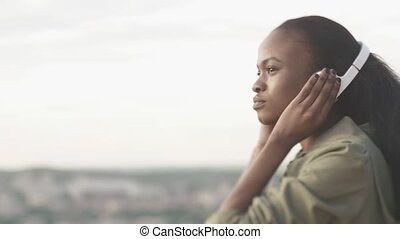 Close-up portrait of young gorgeous black lady listening music in earphones on blurred city background. Moment of true relaxing