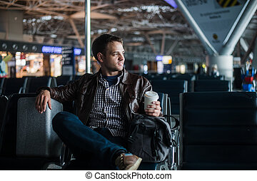 Young attractive man at the airport with his bag suitcase and coffee