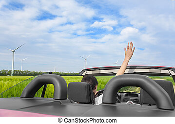 Woman in a red cabriolet in a field with wind power - Woman...