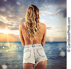 Sexy sunset - Girl with shorts looks at the sea