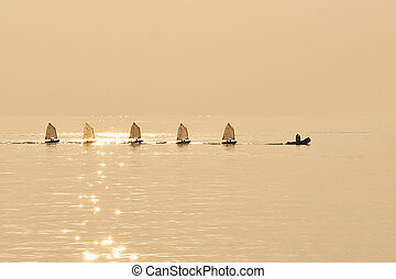 Group of Optimist sails towed into port bu rubber boat -...