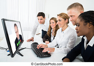 Businesspeople Videoconferencing On Computer - Group Of...