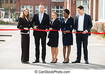 Businesspeople Cutting Ribbon
