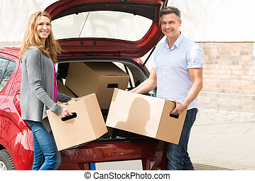 Couple Putting Cardboard Box In Car Trunk - Mature Happy...