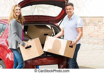 Couple Putting Cardboard Box In Car Trunk - Mature Happy...