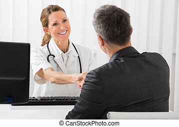 Doctor Shaking Hands With Businessman