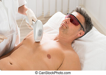 Beautician Giving Laser Epilation Treatment To Man -...