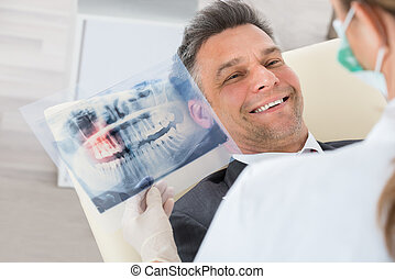 Dentist With Teeth X-ray In Front Of Businessman