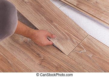 Installing laminate flooring. Carpenter lining parquet boards to
