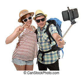 young attractive and chic American couple taking selfie...