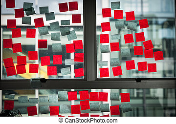 Office window used to ideas board with red and blue sticky...