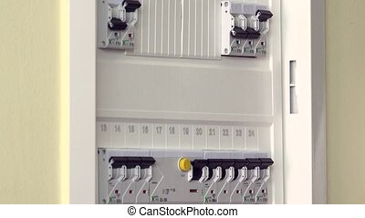 Hand checking and turning on circuit breakers in electrical...