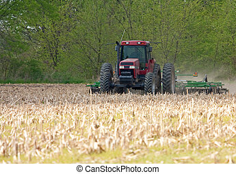 Plowing Farmfield - Tractor pulling a plow in a farmfield
