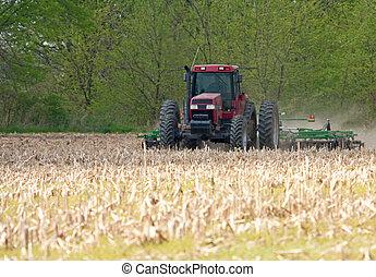 Plowing Farmfield - Tractor pulling a plow in a farmfield