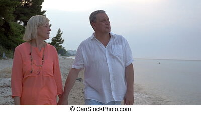 Adult couple walking on beach and talking Evening