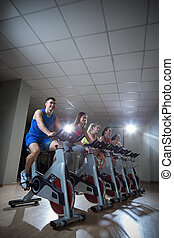 Sportsmen - Active people on a cycle indoors