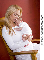 Mother holding newborn baby in rocking chair - Happy young...