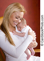 Mother holding newborn baby in rocking chair - Contemplative...