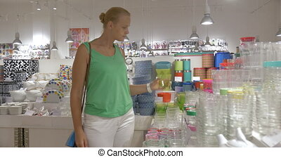 Woman looking at glasses in the store - Young woman in the...
