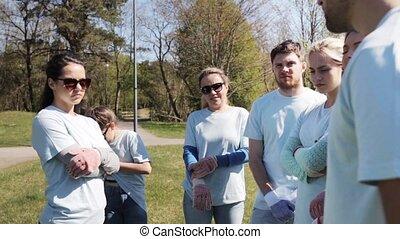 group of volunteers listening to mentor in park -...