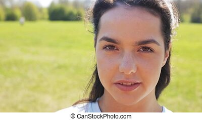 face of happy smiling young woman outdoors - people, emotion...