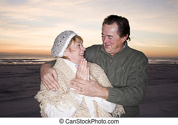 Affectionate senior couple in sweaters on beach
