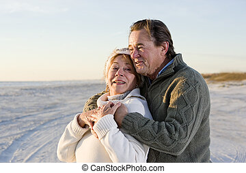 Affectionate senior couple in sweaters on beach -...