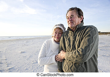 Senior couple in sweaters together on beach - Affectionate...