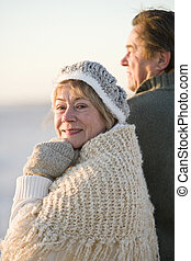 Happy senior couple wearing winter hat and sweater - Senior...