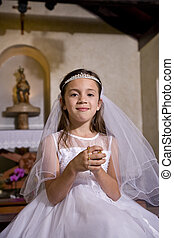 Young girl in church wearing first communion dress -...