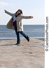 Woman Dancing at the Beach - A young woman with red...
