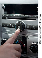 Car Stereo System - A female hand pushing the power button...