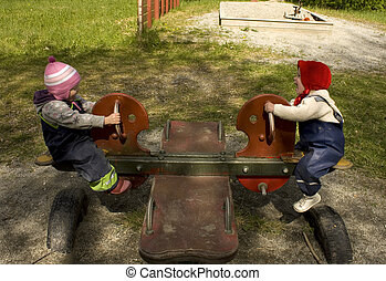 Children playing on a teeter totter in a playground.