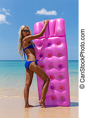 Slim woman with pink swimming mattress on tropical beach