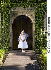 Beautiful child in white dress outside chapel door -...