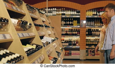 Young Beautiful Smiling Couple Choose Wine In The...