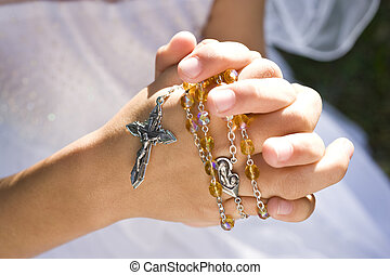 Hands of child holding rosary beads and cross