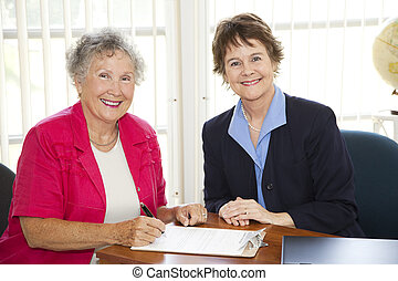 Senior Woman Signing Paperwork - Senior woman signs...