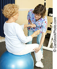 Physical Therapy with Yoga Ball - Senior woman on yoga ball,...