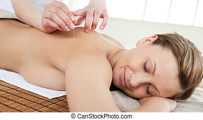 Acupuncture needles on a beautiful woman\'s back in a Spa...
