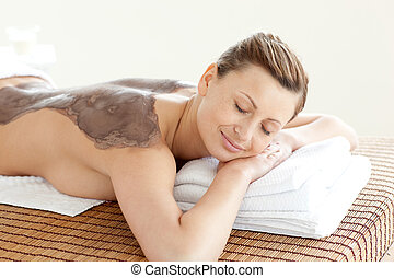 Positive woman enjoying a mud skin treatment in a Spa center