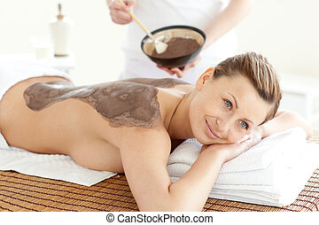 Happy woman enjoying a mud skin treatment in a Spa center