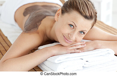 Beautiful woman enjoying a mud skin treatment in a Spa...