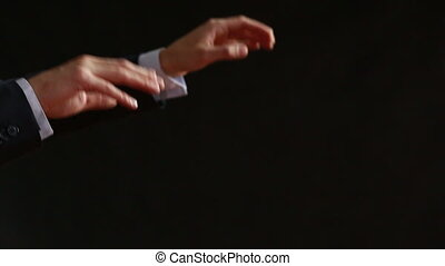 The moving hands of an orchestra conductor directing the...