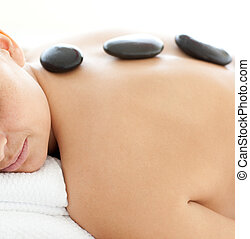 Bright woman lying on a massage table having a stone therapy...