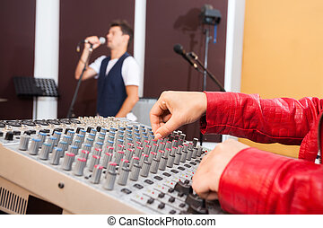 Hands Working On Music Mixer While Man Singing - Closeup of...