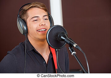 Singer Performing While Looking Away In Studio - Handsome...
