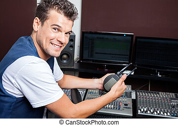 Portrait Of Young Man Holding Headphones At Mixing Table